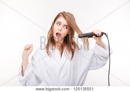 Scared pretty young woman in bathrobe using hair straightener over white background