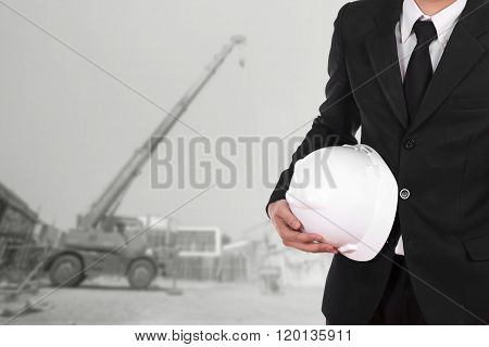 Engineer Holding Helmet With Construction Crane Background