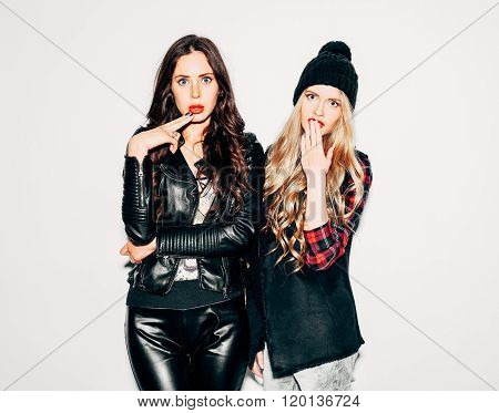 Surprised Two young girls friends standing together nex to white wall and having fun. Showing signs