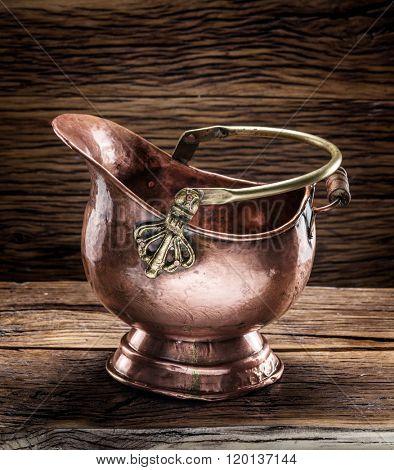 Empty brazen bucket on the wooden table.