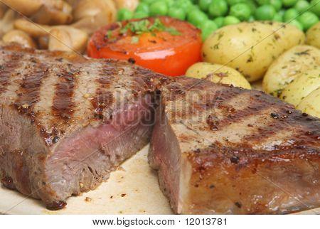 Seltene Sirloin-Steak mit neuen Kartoffeln, Erbsen und Pilzen.