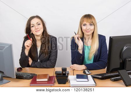 Two Business Women Sitting At A Desk, Holding Pen In Hand And Look To The Frame