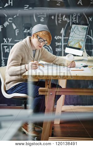 High school male student sitting by the desk at math class