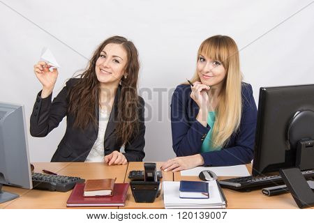 Two Young Women Working In The Office, One Made A Paper Plane, The Second Stares Into The Frame