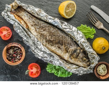Grilled sea bass fish on the gray table.