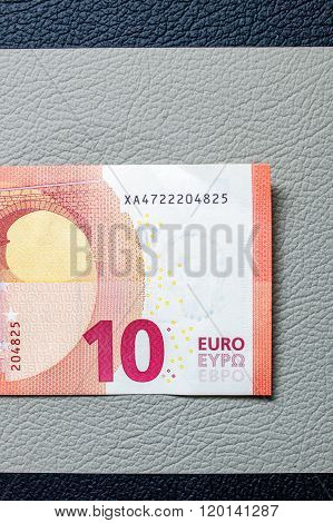 Ten Euro paper currency detail on leather seats of a sport car