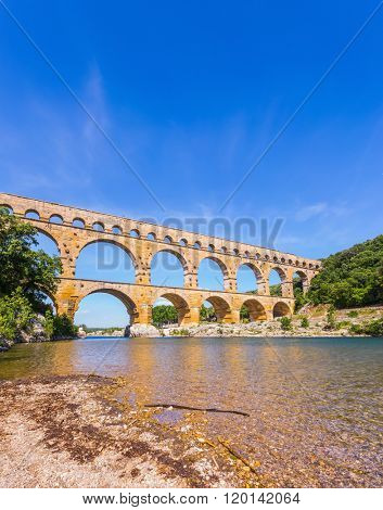 Three-tiered aqueduct Pont du Gard - the highest in Europe. The bridge was built in Roman times on the river Gardon. Provence, spring sunny day