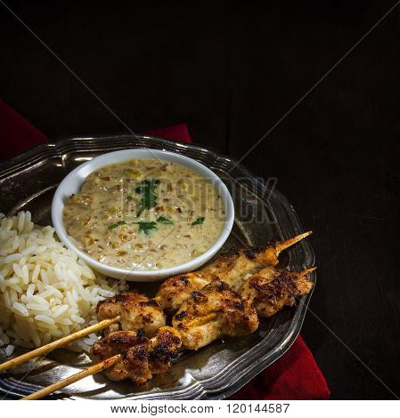 Asian Satay Chicken Skewers With Rice And Peanut Sauce On A Silver Vintage Plate On Dark Rustic Wood