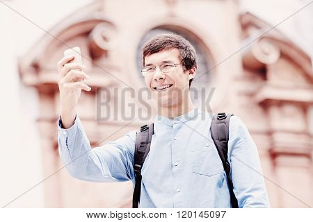 Young hispanic man wearing glasses, jeans shirt and backpack taking picture of himself with smartphone near cathedral in city centre outdoors - travel concept