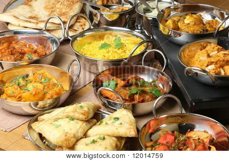 Selection of Indian food including curries, rice, samosas and naan bread.