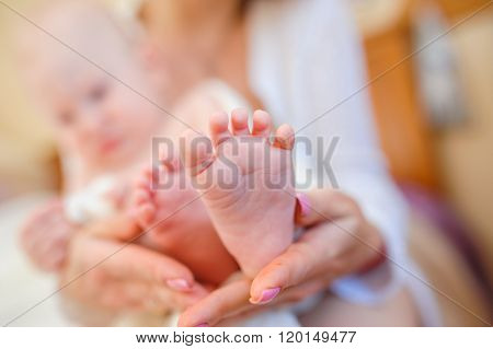 Happy young mother holding little feet of her son