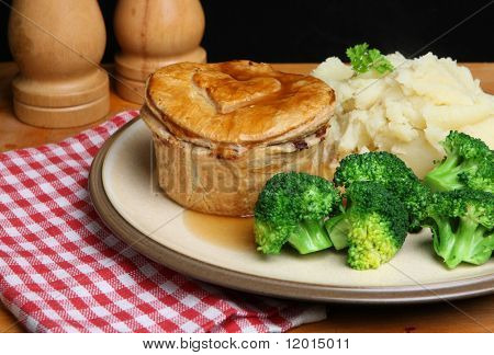 Steak & kidney pie with mashed potato, broccoli and gravy.