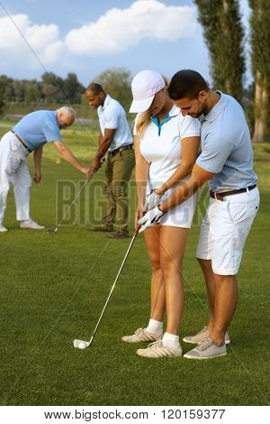 Male instructor teaching female golfer to hit the golf ball.