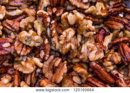 Preparing pecan nuts and walnuts in butter water garlic rosemary sugar ready for roasting.