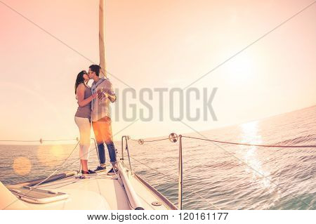 Rich Young Couple In Love On Sailboat Cheering At Sunset - Happy Wander Lifestyle Concept