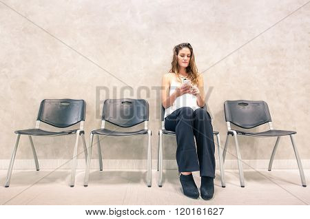 Pensive Young Woman With Mobile Smart Phone Sitting In Waiting Room - Female Person Using Phone