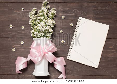 Cutter Flowers With Ribbon Are In The Vase Beside Of Notebook