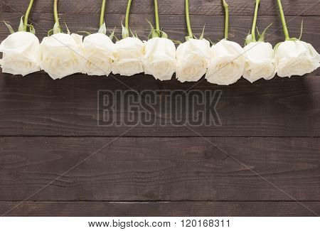 The Arrangement Of White Roses Flower Are On The Wooden Background