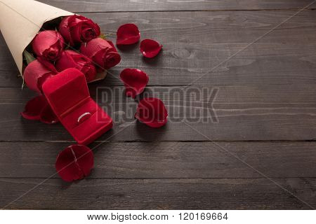 Ring Is Beside Of The Red Roses Flower On The Wooden Background