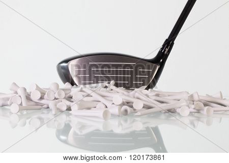 Golf driver and wooden tees on a glass table