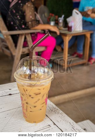 Ice Coffee In Plastic Glass On Old Wooden Table