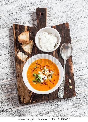 Healthy Quinoa Carrot Soup With Feta Cheese, Seeds And Nuts On Rustic Light Wooden Board. Delicious