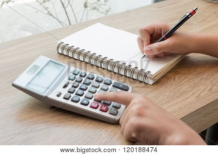 Concept Of Woman Hand Writting On Notebook With Pencil And Calculator