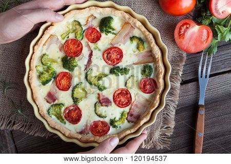 Classic quiche lorraine tart pie with broccoli, bacon and tomatoes