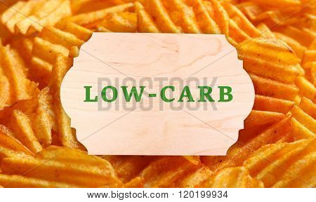 Text Low-Carb on wooden frame on fried potatoes background