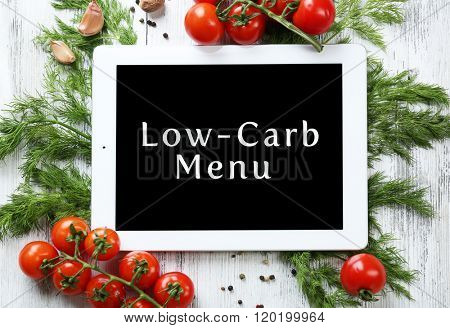 Low-Carb Menu on tablet pc screen with fresh herbs and vegetables on wooden background