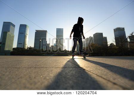 silhouette of skateboarder skateboarding at sunrise city