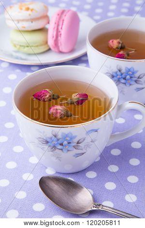 Cups of herbal tea with macaroons on polka dot towel