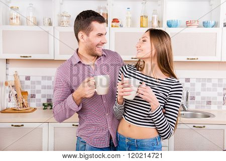 Happy Man And Woman Drinking Coffee In The Kitchen And Hugging