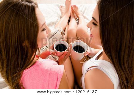 Two Girls With Cups Of Coffee In Hands, Top View Photo