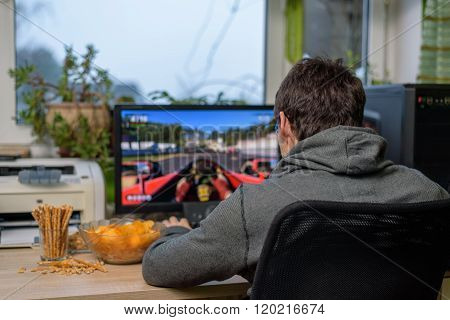 Male Gamer Playing Racing Game On Computer With Snacks Lying On Table