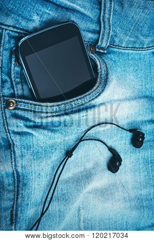 earphones and smart phone on blue jeans background closeup
