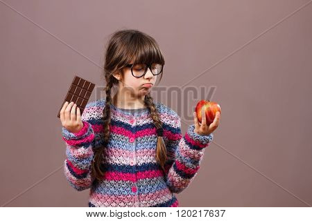 Little girl holding apple and chocolate