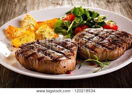 Grilled beefsteaks and vegetables