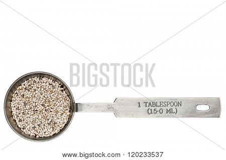 white chia seeds  in a metal measuring tablespoon isolated on white