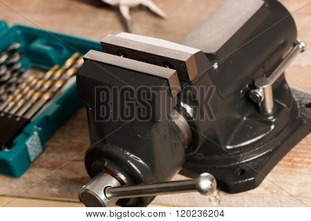 Closeup Of Vice Tool Clamping Device On Wooden Background.