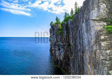 View of big long rocky cliff standing in Cyprus lake against blue bright sky background