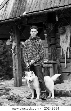 handsome young hipster portrait, young  man standing together with white husky dog in front of old vintage retro wooden house