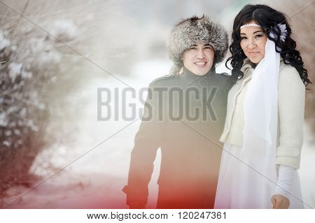 Winter wedding, exotic Asian couple newlyweds, groom in fur hat, bride wearing winter coat.