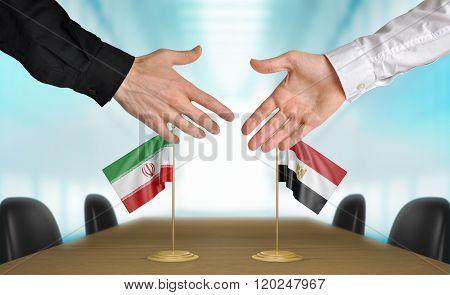 Iran and Egypt diplomats shaking hands to agree deal