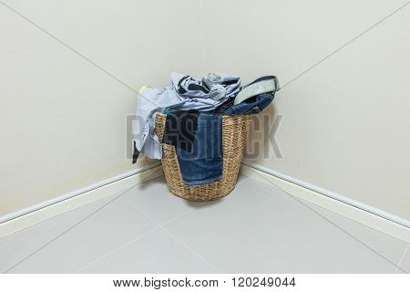 Used Clothes In Wood Basket At Corner In Room