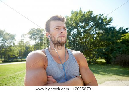 fitness, sport, training and lifestyle concept - young man with earphones listening to music at summer park