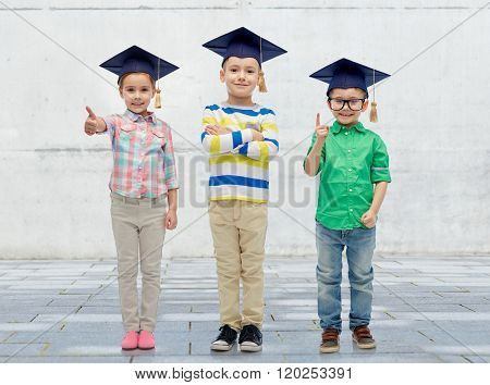 childhood, school, education, knowledge and people concept - happy children in bachelor hats or mortarboards and eyeglasses over urban concrete background