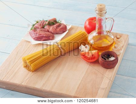 Spaghetti On Wooden Surface With Tomatoes, Mushrooms, Meat And Oil