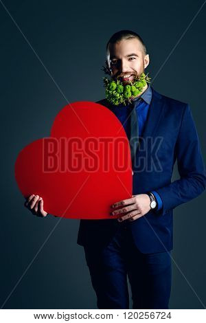 Elegant young man with a beard of green flowers holding red heart and  smiling at camera. Love concept. Valentine's Day. Barbershop.