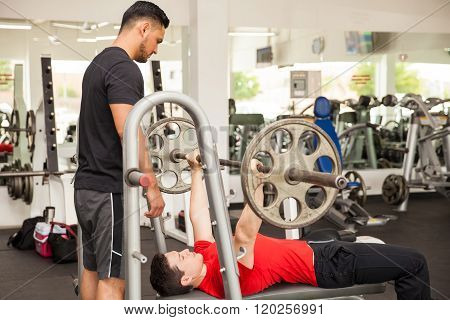 Trainer Spotting A Man At The Gym